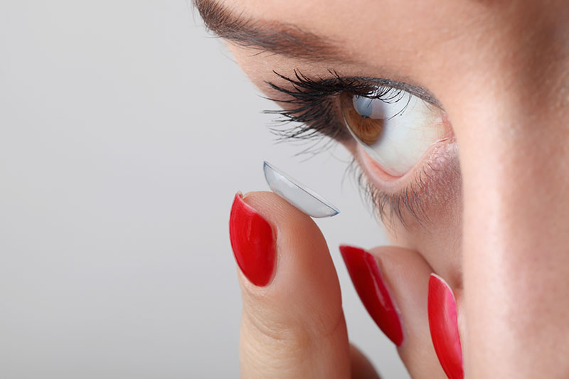white female inserting a contact lens